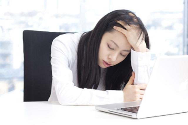 辛い頭痛で仕事に集中できない女性